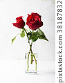 Red fresh roses on the white table 38187832