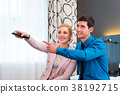 Couple switching TV with remote control in hotel 38192715