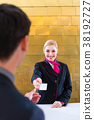 Hotel receptionist check in man giving key card 38192727