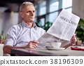 Astonished mature man looking through newspaper 38196309