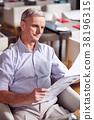 Glad mature man glancing through newspaper 38196315