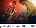 Rock band performs on stage. Guitarist, bass guitar and drums. 38209969