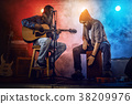 Rock band performs on stage. Guitarist, bass guitar and drums. 38209976