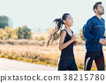 sporty woman and man running along rural road 38215780