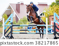 Young rider man jumping on equestrian competition 38217865