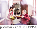 Son and senior father in wheelchair cooking in the 38219954
