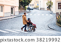 Senior father in wheelchair and young son on a 38219992