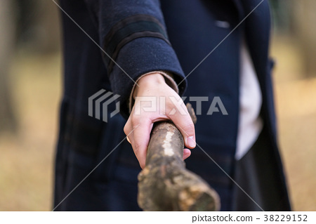 Woman holding a wooden stick 38229152