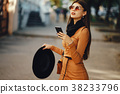 stylish girl walking through the city while using 38233796