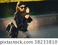 stylish girl walking through the city while using 38233810