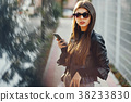 stylish girl walking through the city while using 38233830
