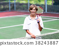 Child playing tennis on outdoor court 38243887