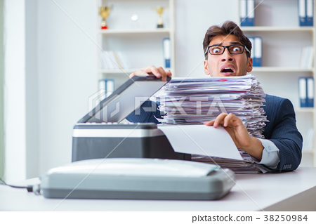 Businessman making copies in copying machine 38250984