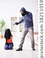 Armed man assaulting young woman at home 38251059