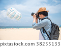 Asian man photographer taking photo on the beach 38255133