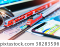 Toy train tickets passport and bank card on laptop 38283596