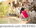 Young woman rock climber climbing on seaside cliff 38293461