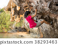 Young woman rock climber climbing on seaside cliff 38293463