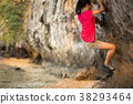Young woman rock climber climbing on seaside cliff 38293464