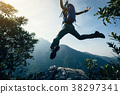 successful female hiker jumping on cliff's edge 38297341
