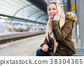 Woman using her phone while waiting for train on 38304365