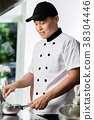 Chef cooking in a commercial kitchen 38304446
