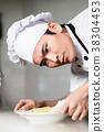 Asian chef plating up a bowl of food 38304453