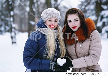 Two girlfriends holding a heart 38304590