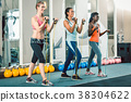 Full length of three fit women exercising with 38304622
