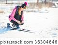 Woman cross country skier putting on ski 38304646