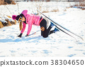 Woman falling while doing cross country skiing 38304650