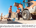 Workers on construction site discussing the use of 38304652