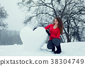Woman with a big snowy heart 38304749