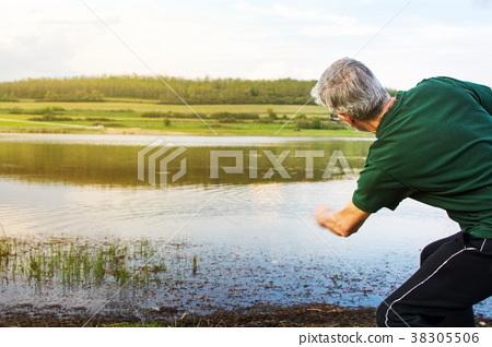 Senior man playing stone skipping at a lake 38305506