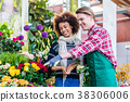 Beautiful woman buying freesias at the advice of a 38306006