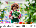 Dedicated woman holding a potted plant during work 38306010