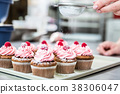 Woman in confectionary icing cupcakes with sugar 38306047