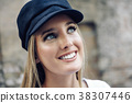 Young blonde woman wearing cap in urban background. 38307446