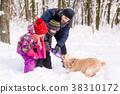Happy family playing with a dog in snow outdoors 38310172