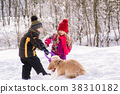 Kids play with dog in winter forest 38310182
