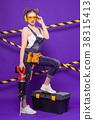 Attractive young builder girl in denim jumpsuit 38315413