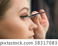 Beautiful woman fake eyelashes by tweezers 38317083