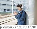 집에서 음악을 들으면서 열차를 기다리는 여자 38317701