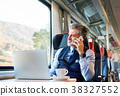 Mature businessman with smartphone travelling by 38327552