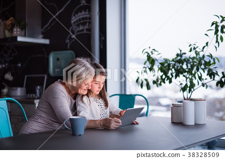 A small girl and grandmother with tablet at home. 38328509