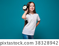 Cute girl in tee shirt with long hair hold the 38328942
