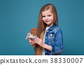 Little pretty girl in jean jacket with long brown 38330007