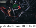 Strong Asia woman execute exercise with exercise-machine in gym. 38331630