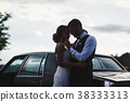Silhouette of bride and groom near car 38333313