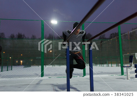 Image of athlete in black hat pulling up on bar in 38341025